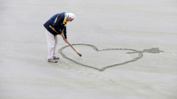 Man drawing heart shape in the sand